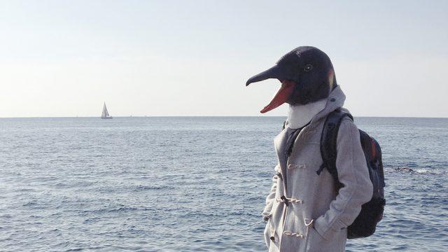 海を背景に二十歳を越した大人がペンギンのマスクをかぶって佇んでいる写真
